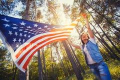 有全国美国国旗的愉快的微笑的少妇户外 免版税库存照片