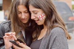有全国英王乔治一世至三世时期旗子的标志的两名妇女在面孔的观看手机的 免版税库存照片