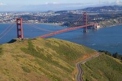 有一条双线道路的金门桥在前景和旧金山在背景中 库存图片