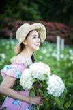 有八仙花属花的领域的美女 图库摄影