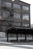 有公共汽车站的被放弃的仓库 图库摄影