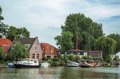 有公园在砖houses's码头停住的树、小船和多云蓝天的Vecht河在韦斯普 库存照片