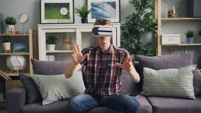 有公平的头发的俊男获得乐趣用虚拟现实玻璃移动的手和头佩带的耳机 人是 影视素材