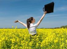 有公文包的女孩在黄色花田 库存图片