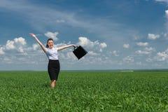 有公文包的妇女走在草的 免版税库存照片