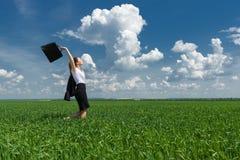 有公文包的妇女走在草的 库存图片