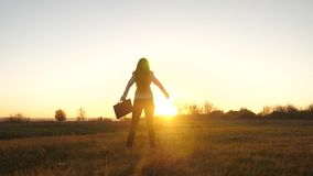 有公文包的自由的女商人在她的手上和在西装是成功在太阳明亮的光芒的日落  股票录像