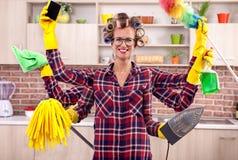 有六手多任务清洁的超级繁忙的年轻主妇 图库摄影