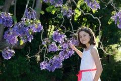 有兰花楹属植物花的女孩 免版税库存图片