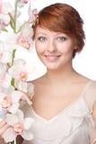 有兰花的年轻微笑的妇女 免版税库存图片