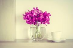 有兰花花瓶的咖啡杯 免版税库存图片