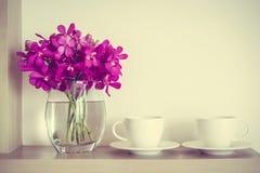 有兰花花瓶的咖啡杯 免版税图库摄影