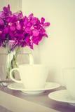 有兰花花瓶的咖啡杯 免版税库存照片