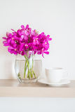 有兰花花瓶的咖啡杯 图库摄影