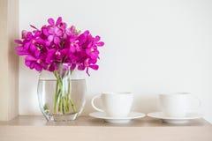 有兰花花瓶的咖啡杯 库存图片