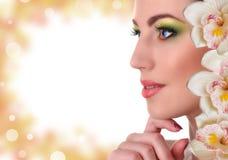 有兰花花的美丽的妇女 图库摄影