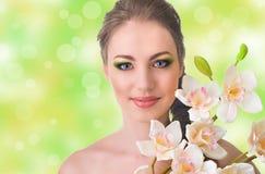 有兰花花的美丽的妇女 库存图片