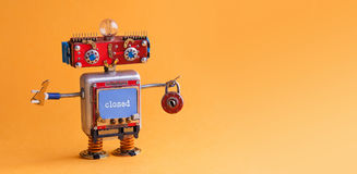 有关键挂锁的友好的机器人玩具在橙色背景 靠机械装置维持生命的人兴高采烈的面孔,红色顶头蓝色显示器身体 数字式 免版税库存图片