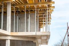 有关闭的新的居民住房建造场所在脚手架和增强木材支持的,建筑concep 库存照片