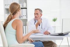 有关医生谈话与他的患者 免版税库存照片