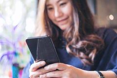 有兴高采烈的面孔的一名美丽的亚裔妇女使用和看一个黑巧妙的电话 免版税库存图片