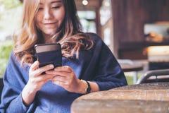 有兴高采烈的面孔的一名美丽的亚裔妇女使用和看一个黑巧妙的电话 库存图片