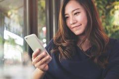 有兴高采烈的面孔的一名美丽的亚裔妇女使用和看巧妙的电话在与绿色垂直的庭院的现代咖啡馆 库存照片