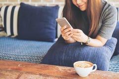 有兴高采烈的面孔的一名美丽的亚裔妇女使用和看巧妙的电话坐有白色拿铁咖啡杯的沙发 图库摄影