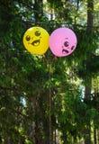 有兴高采烈的面孔的黄色和紫色气球在森林里 图库摄影