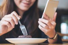 有兴高采烈的面孔藏品和使用的巧妙的电话一名亚裔妇女,当吃在木桌上时的果仁巧克力 库存照片