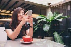 有兴高采烈的面孔藏品和使用的巧妙的电话一名美丽的亚裔妇女有在玻璃桌上的一个红色咖啡杯的在现代咖啡馆 库存图片