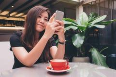 有兴高采烈的面孔藏品和使用的巧妙的电话一名美丽的亚裔妇女有在玻璃桌上的一个红色咖啡杯的在现代咖啡馆 图库摄影