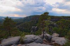 有典型的岩石峰顶的风景全景,古老森林在多云天空下 漂泊瑞士国家公园 免版税库存照片