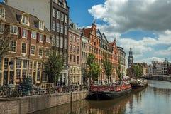 有典型的房子的宽运河,尖顶,在阿姆斯特丹停泊了小船和蓝天 免版税库存图片