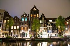 有典型的荷兰房子和居住船的阿姆斯特丹运河Singel在夜之前 库存照片