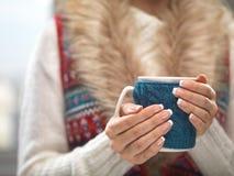 有典雅的法式修剪钉子的妇女手设计拿着一个舒适被编织的杯子 冬天和圣诞节时间概念 免版税库存照片