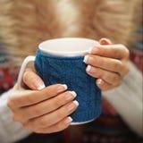 有典雅的法式修剪钉子的妇女手设计拿着一个舒适被编织的杯子 冬天和圣诞节时间概念 免版税库存图片
