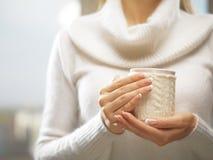 有典雅的法式修剪钉子的妇女手设计拿着一个舒适被编织的杯子 冬天和圣诞节概念 库存照片