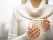 有典雅的法式修剪钉子的妇女手设计拿着一个舒适被编织的杯子 冬天和圣诞节概念 免版税库存图片