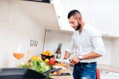 有典雅的衬衣的人烹调女朋友的晚餐 关闭厨房厨师切口菜和准备沙拉 免版税库存图片