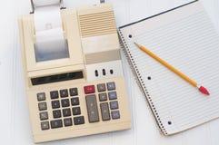 有写字板的老计算器和铅笔做的办公室关系了工作或家预算,水平。观看从上面上面。 库存照片