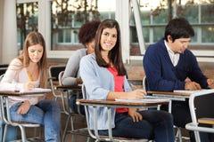 有写检查的学生的妇女在教室 免版税库存照片