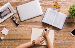 有写给笔记本的书的手在桌上 免版税库存照片