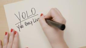 有写yolo您的红色指甲油的少年女性手在与黑标志的白皮书只居住,一旦诱导引述- 股票视频