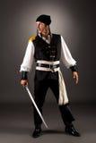 有军刀的大胆的海盗 在灰色背景的照片 免版税库存照片
