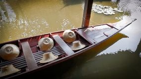 有农夫` s帽子的浮动木小船靠码头和栓与柱子 免版税库存照片