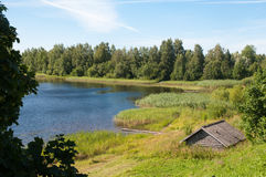 有农村房子的蓝色湖 图库摄影