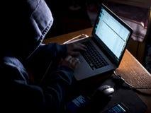 有冠乌鸦的Anonimous人在黑暗的演播室键入的文本在网上在有拷贝空间的互联网上 免版税图库摄影