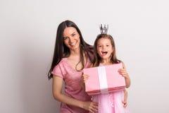 有冠头饰带的一个小女孩和她的拿着一个礼物的母亲在演播室 免版税库存照片