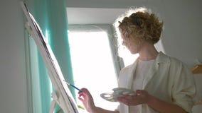 有冥想的富启示性的画家妇女绘与明亮的颜色的画在画架的白色帆布在艺术课反对被日光照射了 影视素材